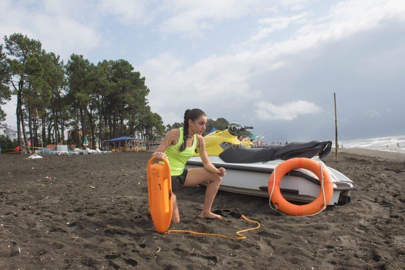 当班女孩的救生员保留浮体在海滩 浇灌滑行车,在海滩的救生员救援设备橙色保管者工具 Saf 免版税图库摄影