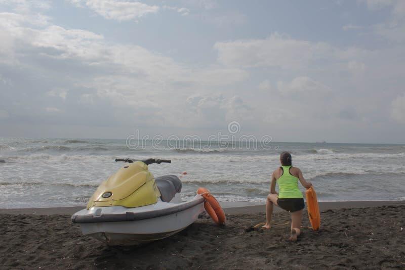 当班女孩的救生员保留浮体在海滩 浇灌滑行车,在海滩的救生员救援设备橙色保管者工具 Saf 库存照片