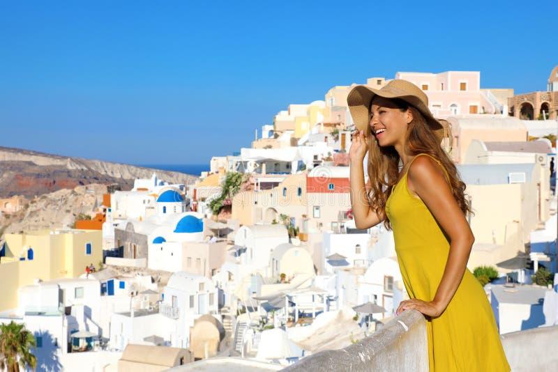 当看从阳台的都市风景在圣托里尼时,可爱的被晒黑的妇女在Oia村庄修理自己与从太阳的帽子 库存照片
