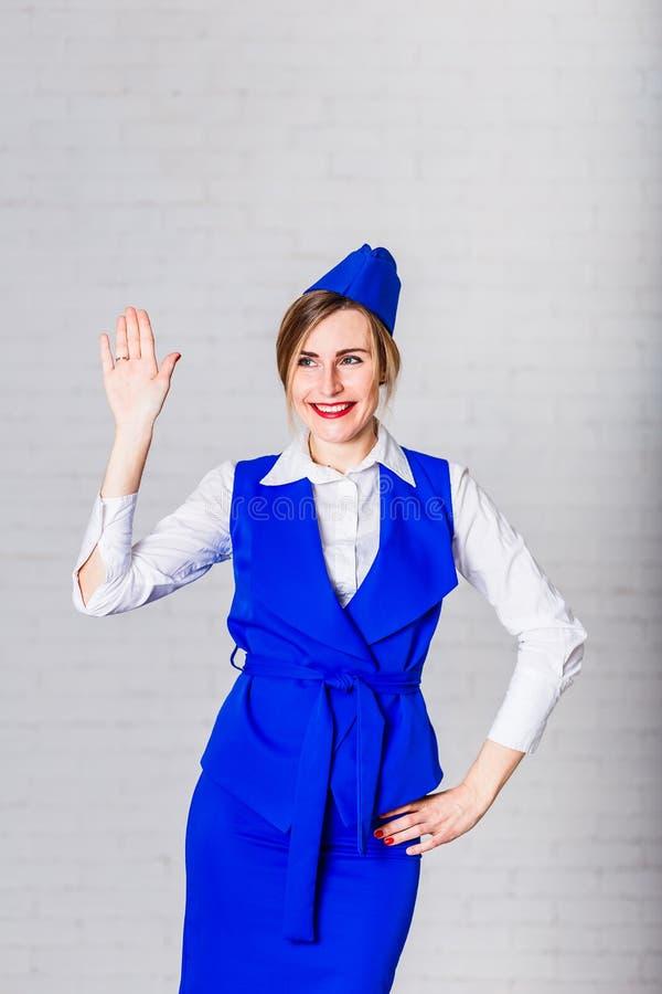 当空服员打扮的快乐的微笑的年轻女人 库存照片