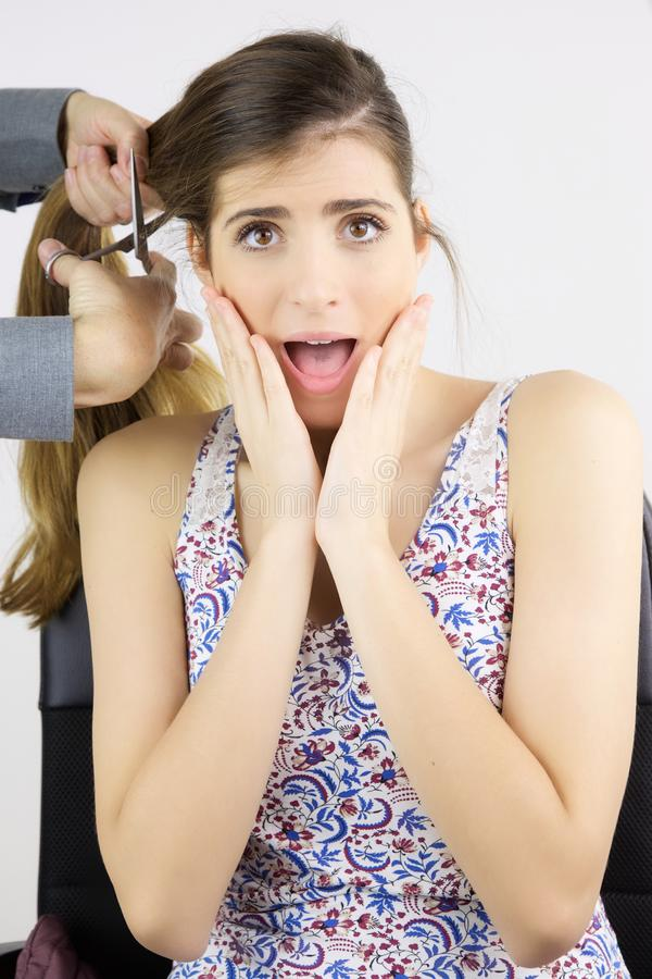当美发师砍她的头发时,妇女惊吓了尖叫 库存照片