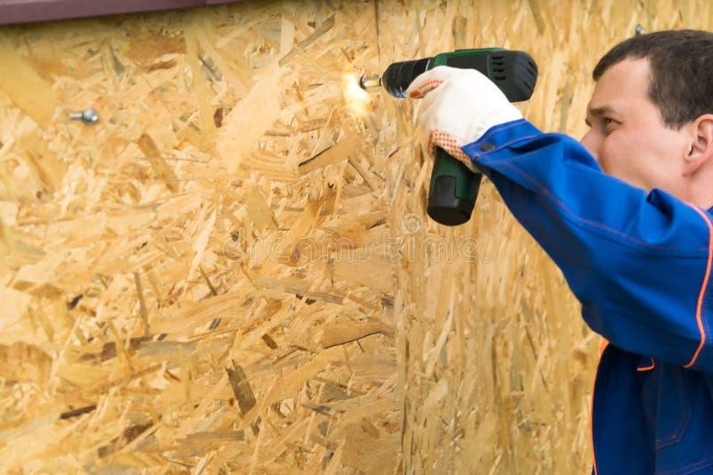 当螺丝刀紧固木盾,在一件蓝色制服的大师运作 免版税库存图片