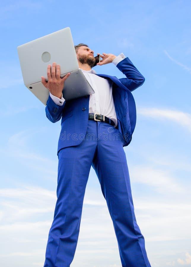 当讲电话蓝天背景时,人穿着考究的商人拿着膝上型计算机 人正式衣服现代技术 库存照片