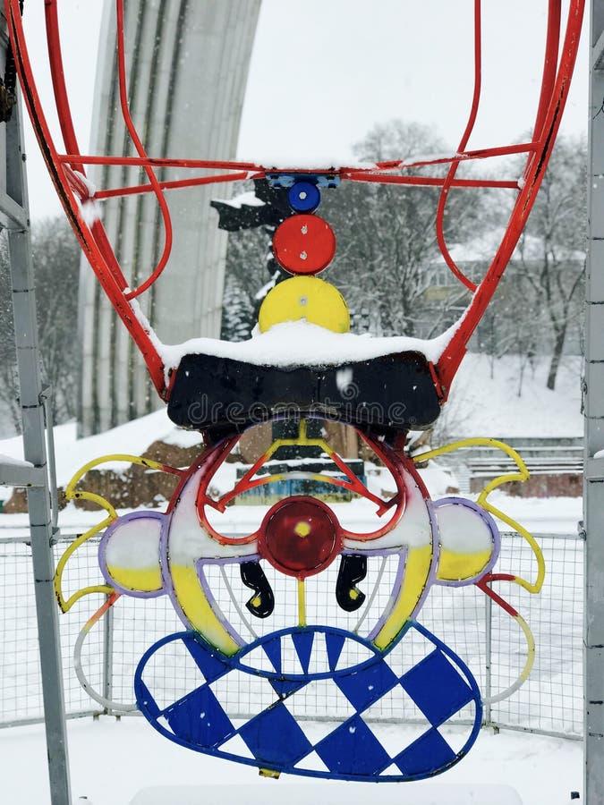 当雪落,一个小狂欢节的上部小丑在Kyiv等待太阳 免版税图库摄影