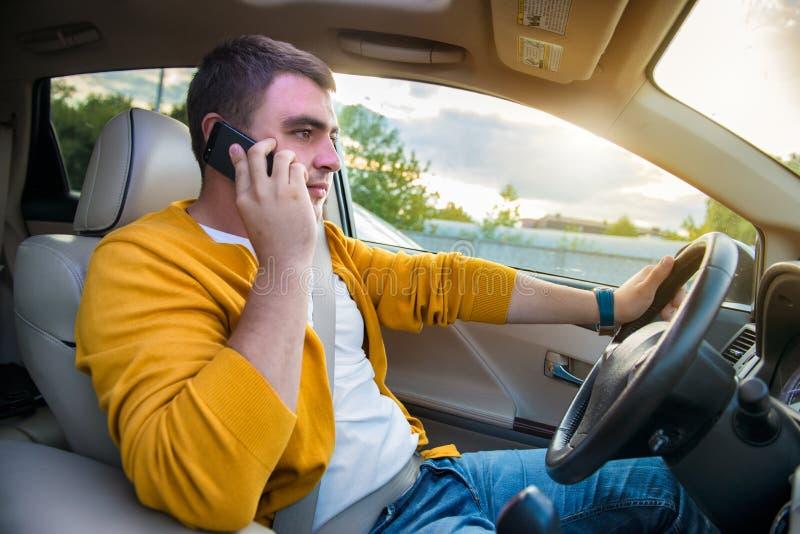 当驾驶汽车时,供以人员谈话在手机 免版税库存图片