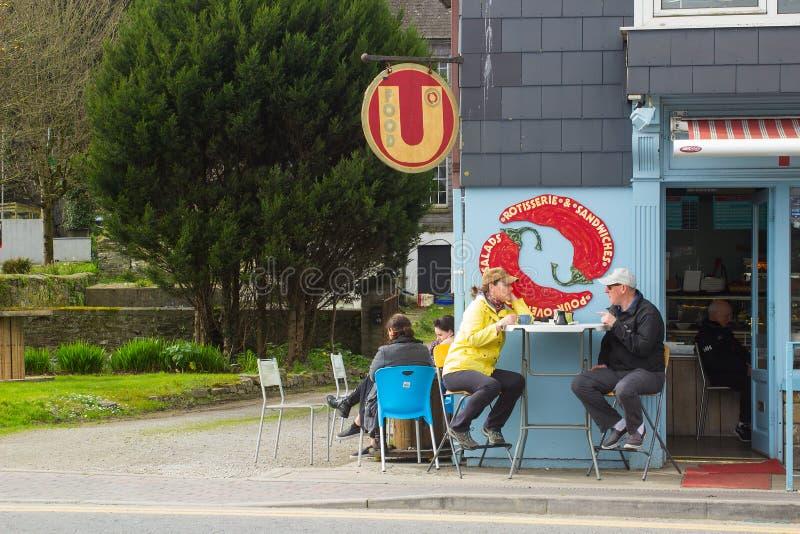 当他们在Kinsale采取快餐户外在科克郡,爱尔兰,吃饭的客人利用早期的春天阳光 免版税图库摄影