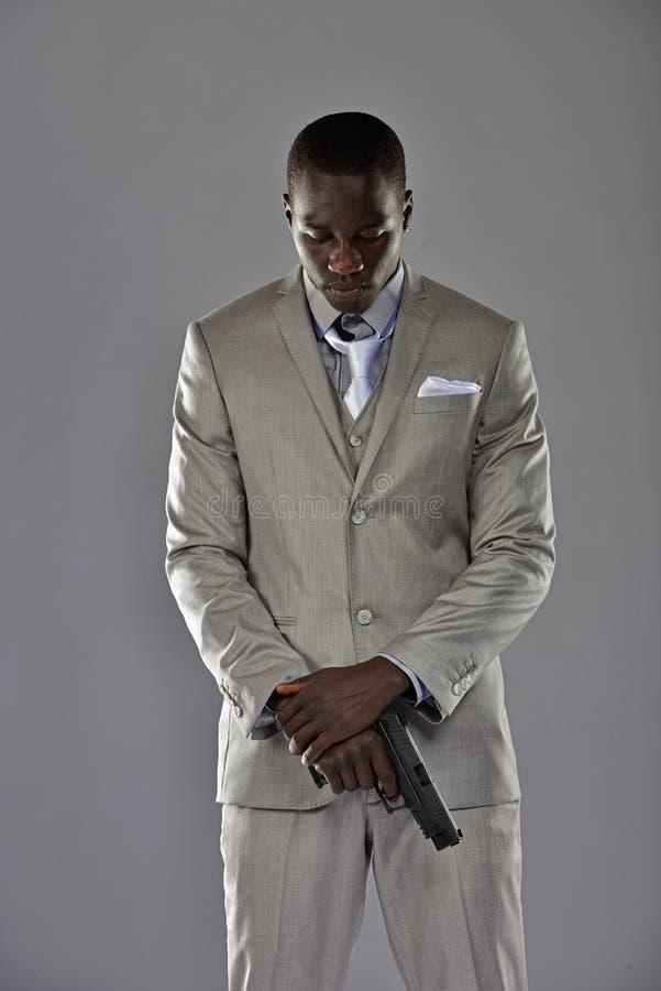 当他拿着他的枪,衣服的人看得下来 免版税库存图片