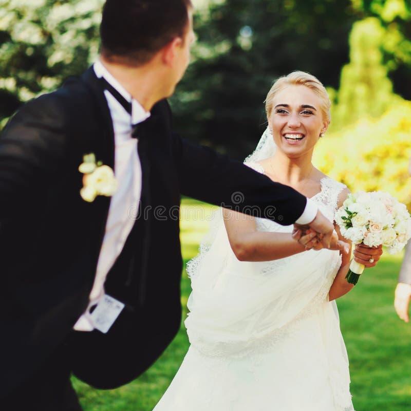 当他们横跨公园时,跑新郎握新娘的手 图库摄影