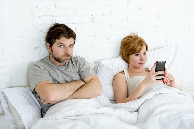 当他的互联网上瘾者妻子使用手机时,在床丈夫的夫妇挫败了翻倒和不满意 库存照片