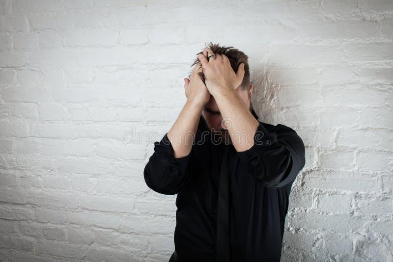 当他遭受消沉和失败,垂头丧气的人拿着他的头 为头疼、金钱麻烦或者家庭暴力使用它 图库摄影
