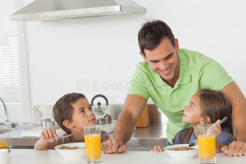 当他们食用早餐时,生谈话与他的孩子 免版税库存照片