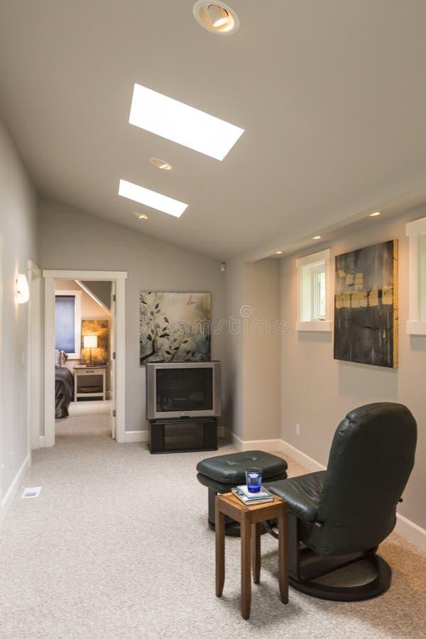 当代高级家庭内部的媒介室与拱顶式顶棚、天窗、皮革躺椅、旁边桌和电视 库存照片