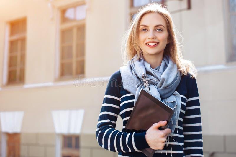 当wallking与触摸板户外时,年轻快乐的女学生享受业余时间 美丽的妇女拿着数字 库存照片