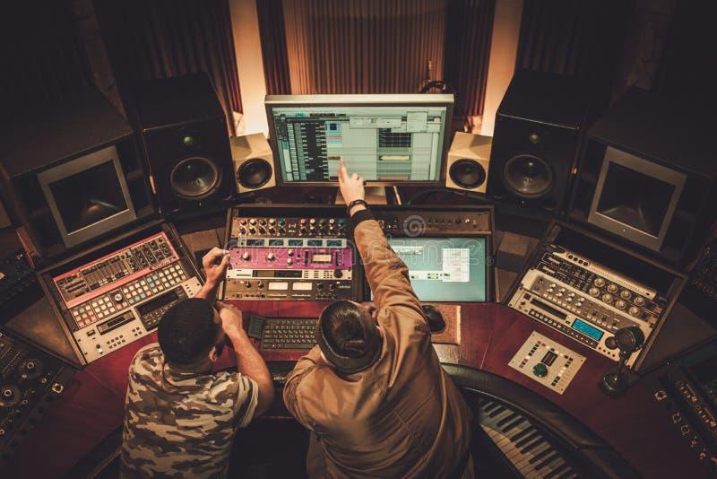 录音师和音乐家在精品店录音的录音歌曲 免版税图库摄影
