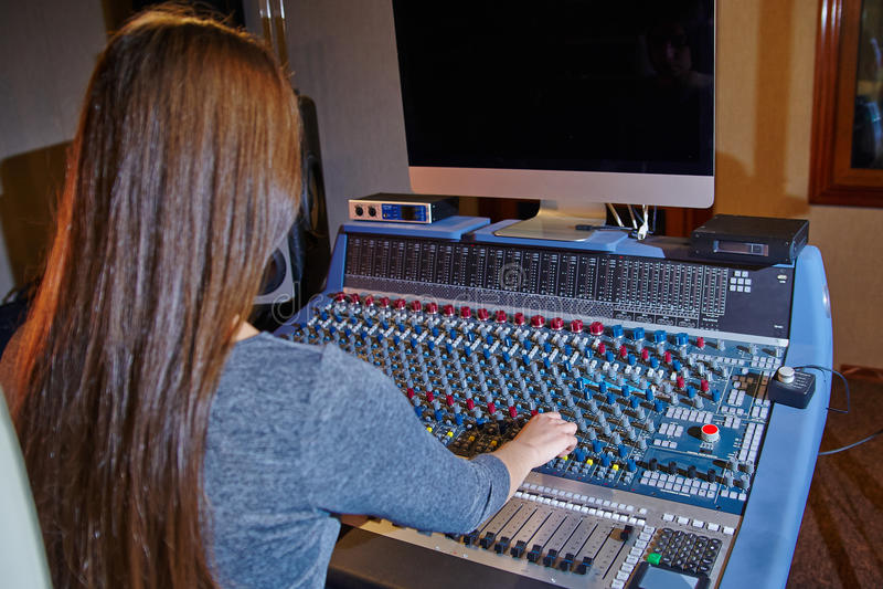 录音师在一个混合的控制台工作 免版税库存照片
