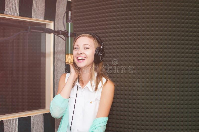录音歌的少妇在一个专业音乐演播室 免版税库存图片