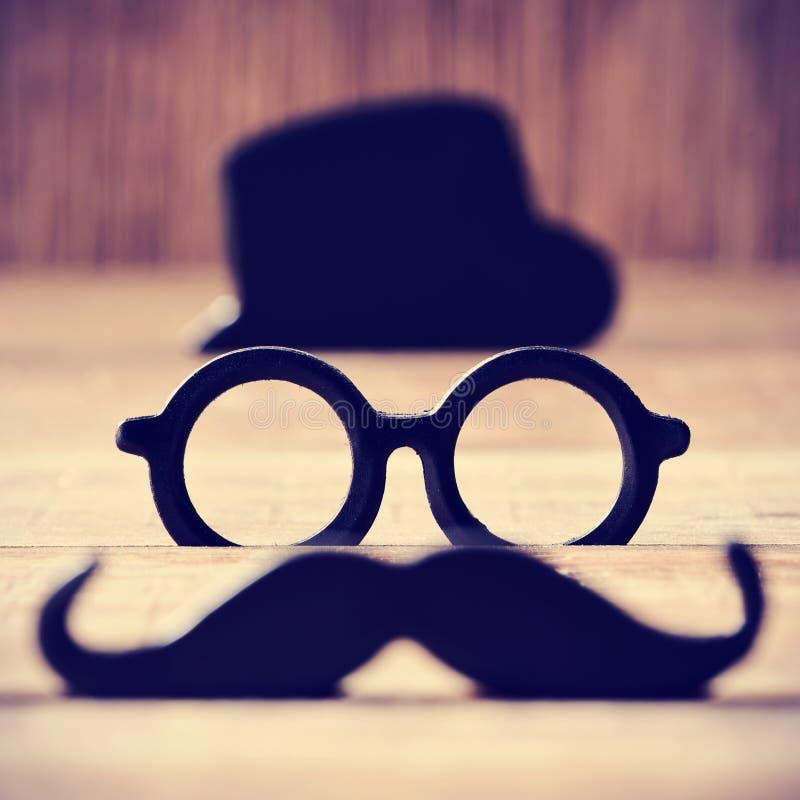 形成一个人的面孔髭、镜片和帽子 免版税库存图片
