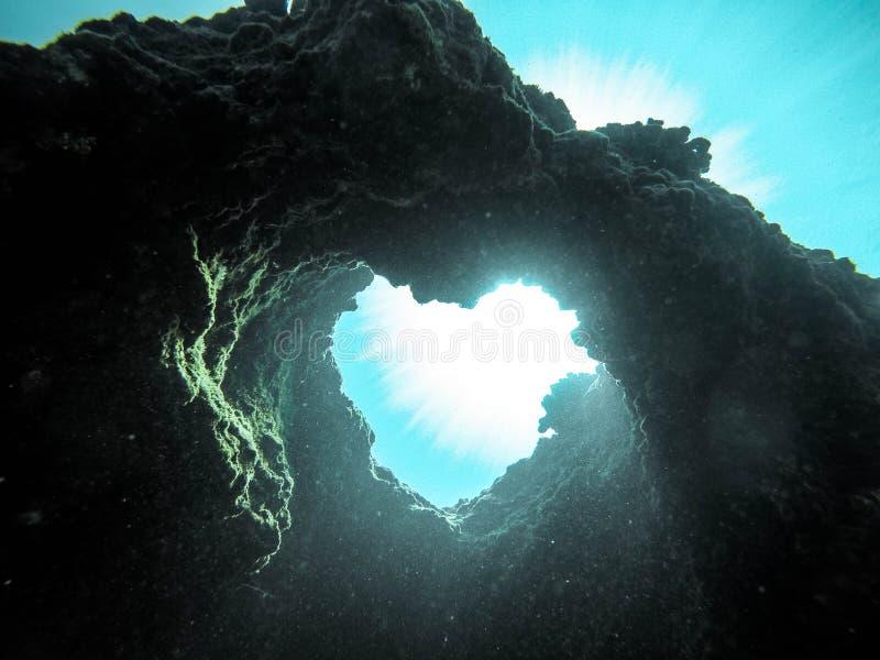 形成一点心脏-美丽的墙纸的珊瑚礁和岩石水下的美丽的射击  免版税库存图片