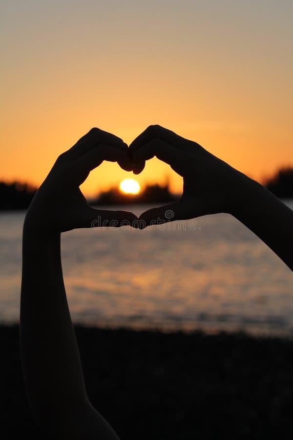 形成与日落的手剪影心脏 免版税库存图片