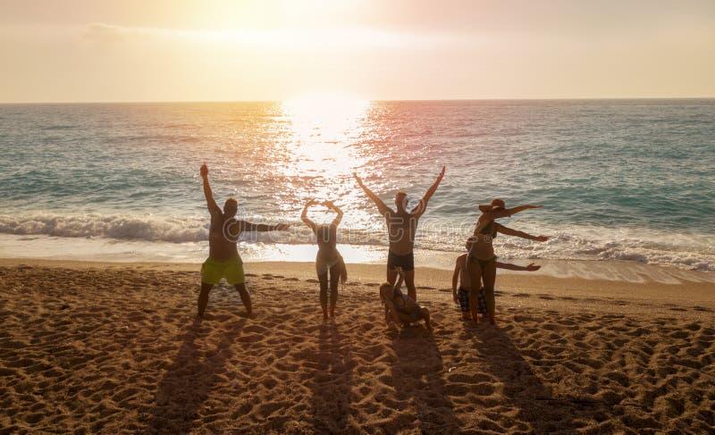 形成在海滩的小组朋友情书在日落 库存图片