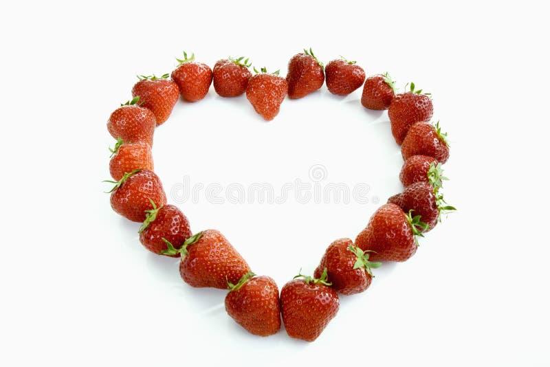 形成在白色的草莓心脏形状 免版税库存图片