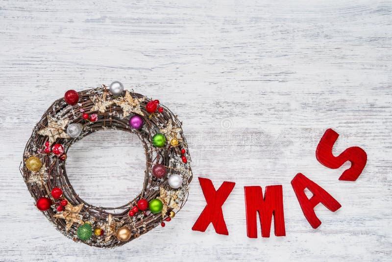 形成在whi的圣诞节花圈和红色木信件词XMAS 图库摄影