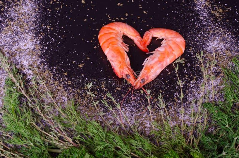 形成心脏用迷迭香、盐和胡椒的两只虾 库存图片