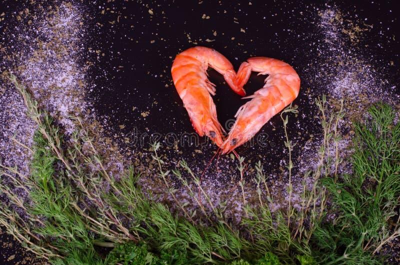 形成心脏用迷迭香、盐和胡椒的两只虾 图库摄影