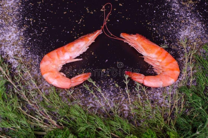形成心脏用迷迭香、盐和胡椒的两只虾 免版税库存图片