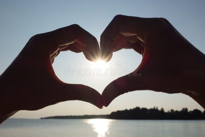 形成心脏的女性手反对在湖的太阳在冬天 免版税库存照片
