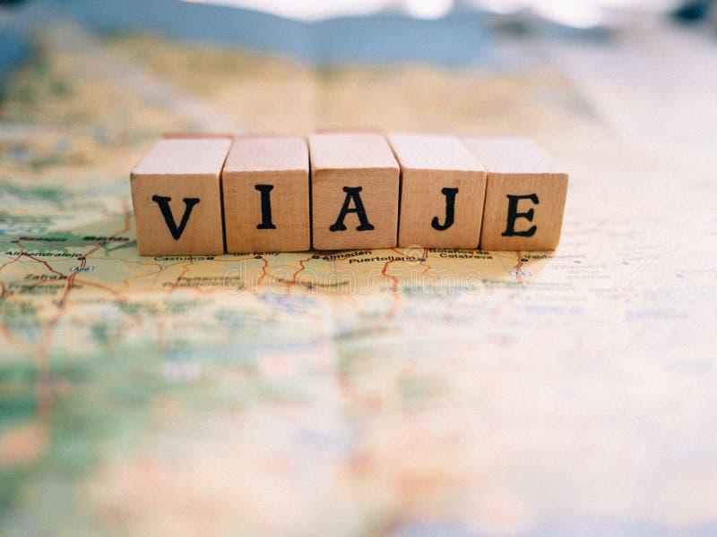 形成词旅行用西班牙语在地图顶部的信件 库存图片