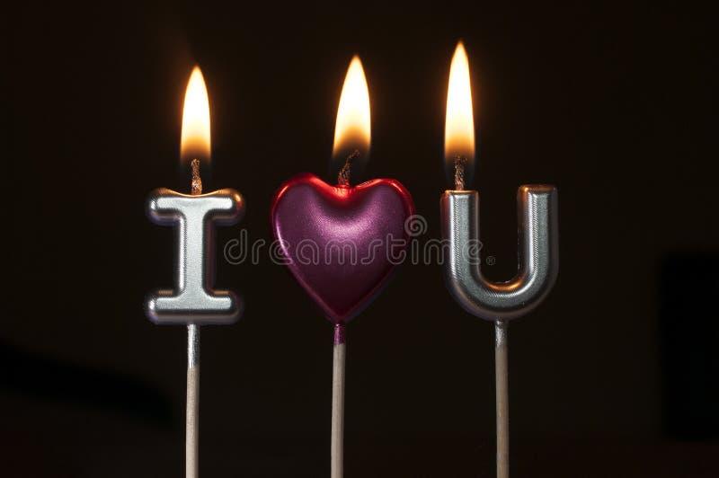 形成词组的银色和桃红色生日蜡烛:我爱你,黑背景 库存照片