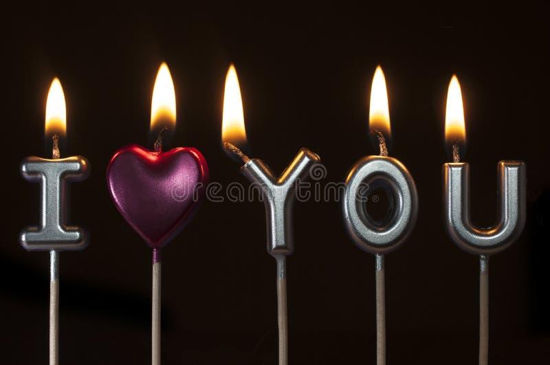 形成词组的银色和桃红色生日蜡烛:我爱你,黑背景 免版税库存图片