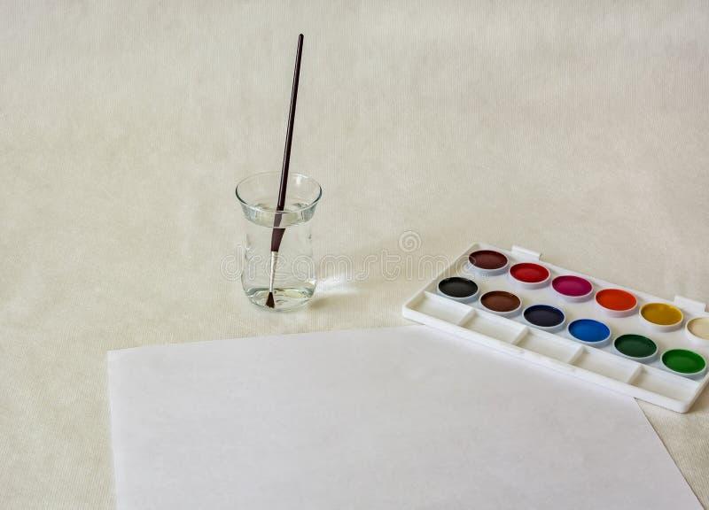 水彩、一杯与刷子的水和白色板料  库存照片