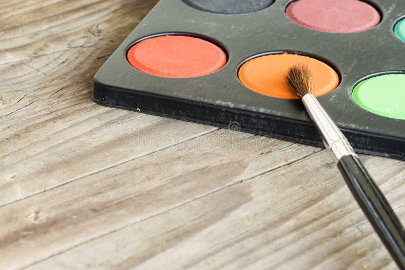 水彩和刷子在木背景 库存图片