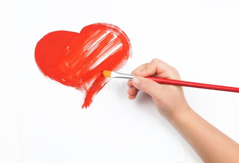 水彩心脏和儿童手有油漆刷的 库存照片