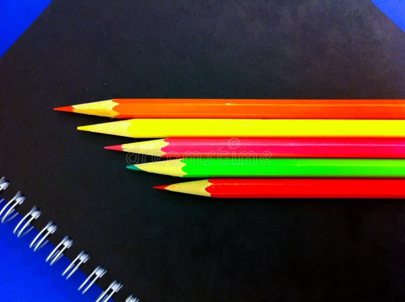 彩色铅笔和书写笔记本 库存照片
