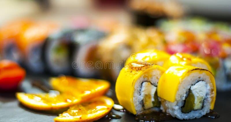 彩虹与三文鱼,鳗鱼,金枪鱼,鲕梨,皇家大虾,乳脂干酪费城,鱼子酱tobica, chuka的寿司卷 寿司菜单 库存图片