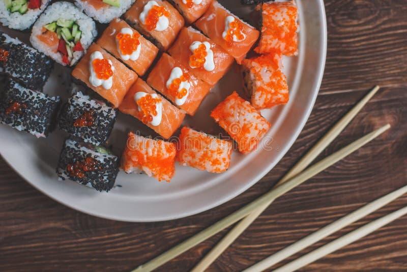 彩虹与三文鱼,鳗鱼,金枪鱼,鲕梨,皇家大虾,奶油奶酪的寿司卷 库存图片