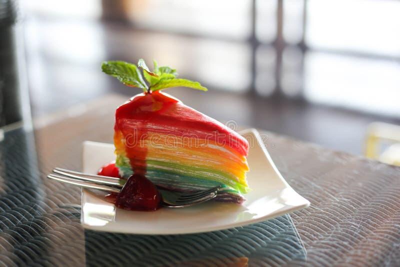 彩虹五颜六色的绉纱蛋糕用草莓调味汁用冷的咖啡 免版税库存图片