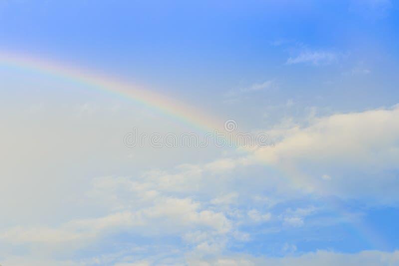 彩虹和太阳发出光线在云彩和蓝天 免版税库存照片