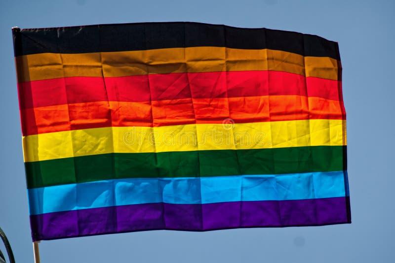 彩虹旗子在天空蔚蓝背景中 库存图片