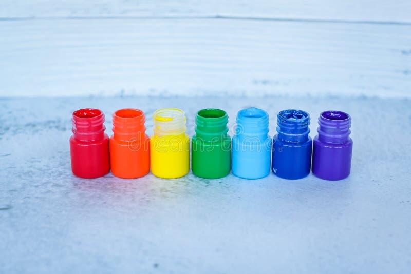 彩虹树胶水彩画颜料或丙烯酸漆在瓶子在白色难看的东西背景,选择聚焦 免版税库存图片