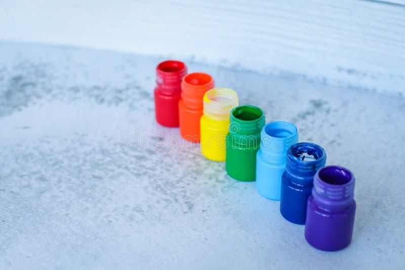彩虹树胶水彩画颜料或丙烯酸漆在瓶子在白色难看的东西背景,选择聚焦 免版税库存照片
