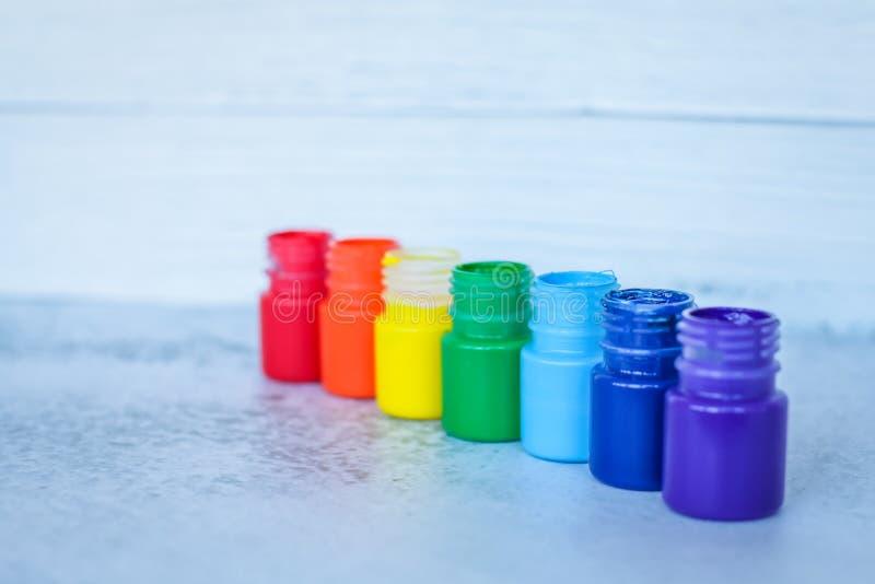 彩虹树胶水彩画颜料或丙烯酸漆在瓶子在白色难看的东西背景,选择聚焦 库存照片