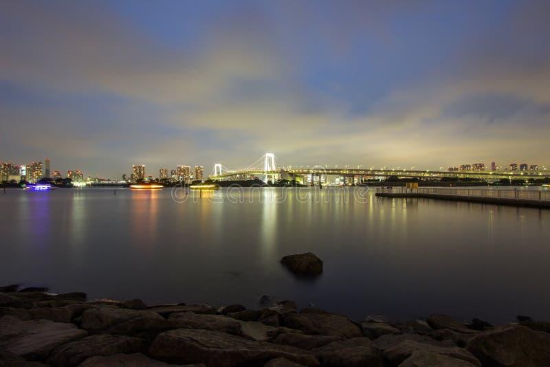 彩虹桥和周围的东京湾地区夜视图如被看见从Odaiba, Minato,东京,日本 库存照片