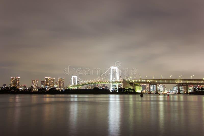 彩虹桥和周围的东京湾地区夜视图如被看见从Odaiba, Minato,东京,日本 免版税库存照片