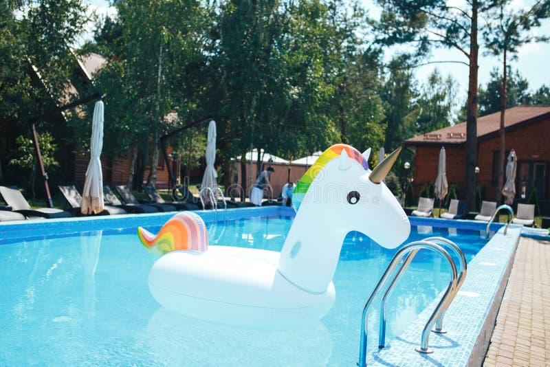 彩虹漂浮在一游泳场的色的可膨胀的独角兽在夏天 在水池的白色可膨胀的独角兽 图库摄影