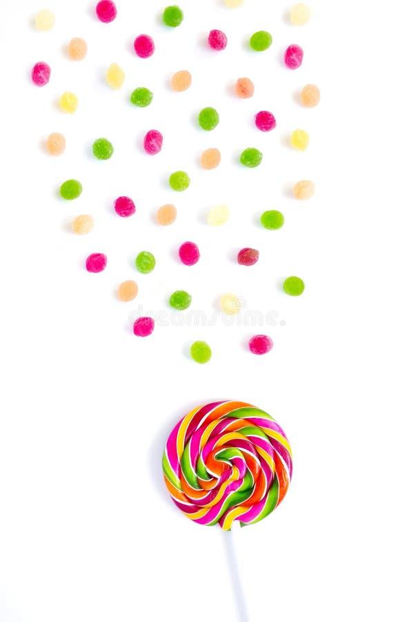 彩虹甜甜明亮的圆的棒棒糖和许多五颜六色在白色背景的一点棒棒糖 库存照片