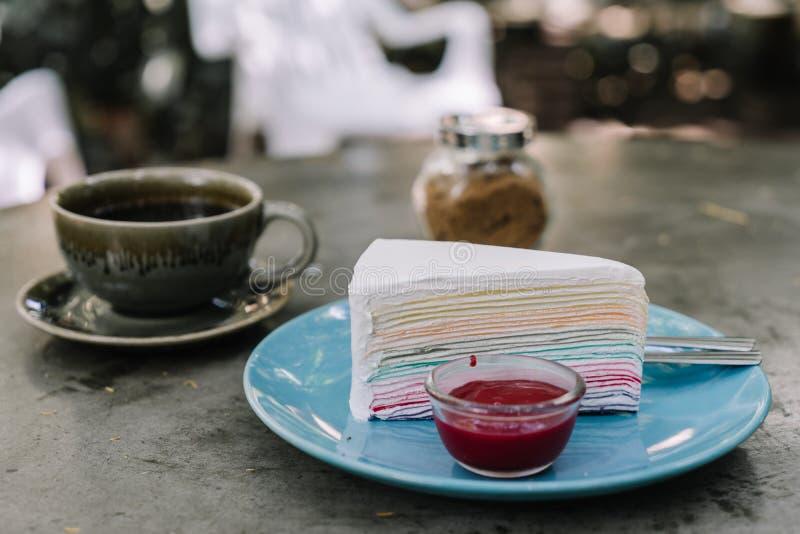 彩虹绉纱蛋糕用在蓝色板材淡色colo的草莓酱 库存图片